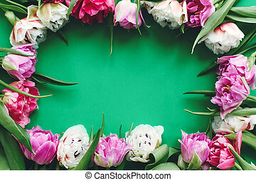 Happy mother's day. Beautiful double peony tulips frame flat lay on green paper, space for text. International women's day. Hello Spring. Stylish Floral Greeting card