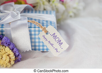 Happy mother's day concept. Beautiful Gift box with purple flower, paper tag  on white cheesecloth background.