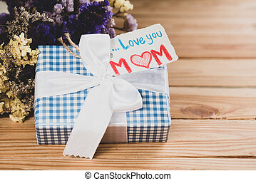 Happy mother's day concept. Gift box with flower, paper tag with Love you MOM text on wooden table background.