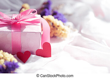 Happy mother's day concept. Gift box with purple flower and two handmade red heart on white cheesecloth background.