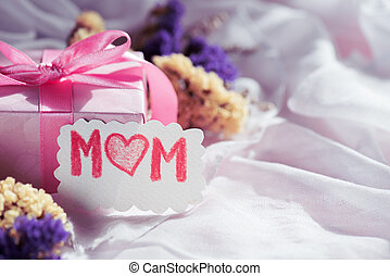 Happy mother's day concept. Gift box with purple flower, paper tag with LOVE MOM text and two handmade red heart on white cheesecloth background.