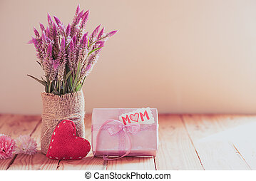 Happy mother's day concept. Gift box with purple flower, paper tag with love mom text and two handmade red heart on wooden table background.