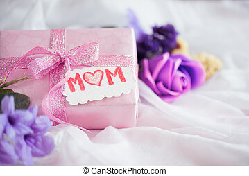 Happy mother's day concept. Gift box with purple flower, paper tag with LOVE MOM text on white cheesecloth background.