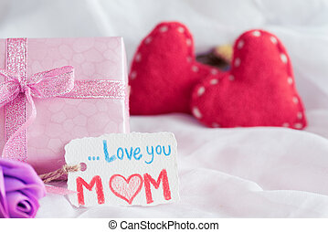Happy mother's day concept. Gift box with purple flower, paper tag with LOVE YOU MOM text and two handmade red heart on white cheesecloth background.