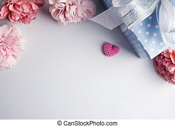 Happy mothers day concept of pink carnation flowers and gift box and heart with copy space
