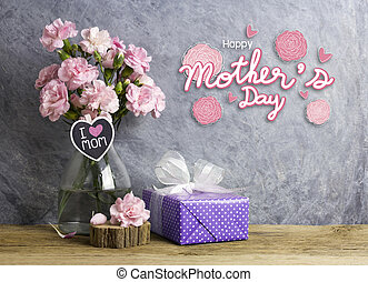 Happy mothers day concept of pink carnation flowers in bottle with i love mom letter on heart wood and violet  gift box