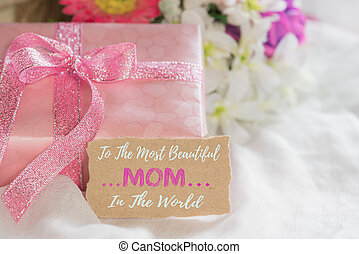 Happy mother's day concept. Pink Gift box with purple flower, paper tag  on white cheesecloth background.
