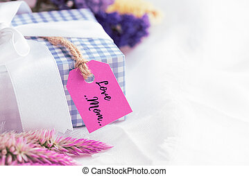 Happy mother's day concept. Pink Gift box with purple flower, paper tag with LOVE MOM text and two handmade red heart on white cheesecloth background.
