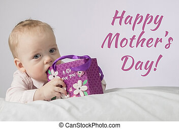 Happy mothers day. Cute 8 month boy with a gift in a pocket lying on the white blanket and looking at camera. Ready Postcard