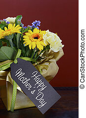Happy Mothers Day gift of Spring Flowers on dark wood table.