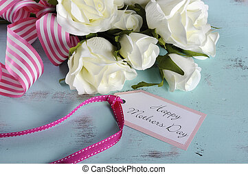 Happy Mothers Day gift of white roses bouquet with pink stripe ribbon and gift tag with greeting on aqua blue vintage shabby chic table.