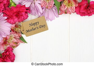 Happy Mothers Day gift tag amongst a corner border of pink flowers against white wood