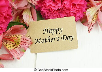 Happy Mothers Day gift tag close up with pink flowers against white wood