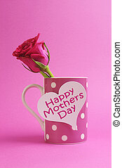 Happy Mothers Day heart gift tag on pink polka dot coffee mug with pink rose bud.