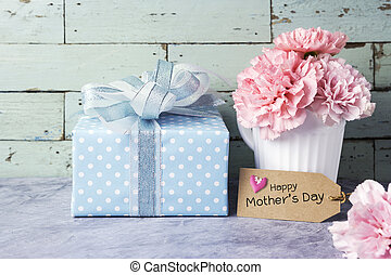 Happy mothers day message on brown paper tag and pink carnation flower in white cup and gift box