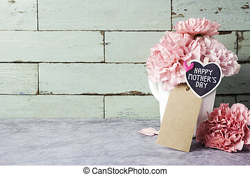 Happy mothers day message on heart wood and pink carnation flower in white cup