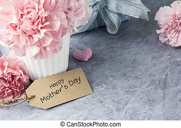 Happy mothers day message on tag and pink carnation flower in white cup