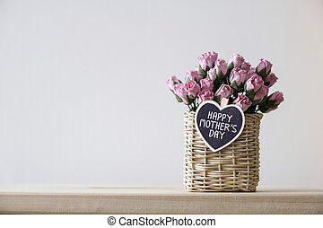Happy mothers day message on wood heart and pink paper roses in basket on the table with copy space minimal style