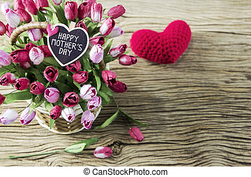 Happy mothers day of pink and red tulip flowers in wood basket with red heart on wood background