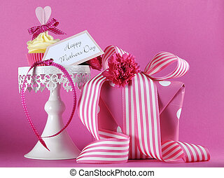 Happy Mothers Day pink heart cupcake on white cupcake stand with gift and greeting gift tag against a feminine pink background.