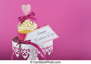 Happy Mothers Day pink heart cupcake on white cupcake stand with greeting gift tag against a feminine pink background, with copy space for your text here..