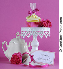 Happy Mothers Day pink heart cupcake on white cupcake stand with greeting gift tag against a feminine pink background.