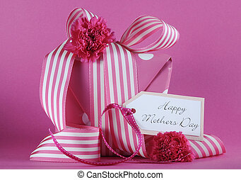 Happy Mothers Day pink polka dot and stripe ribbon gift and greeting gift tag against a feminine pink background.