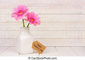 Happy Mothers Day tag with pink flowers against white wood