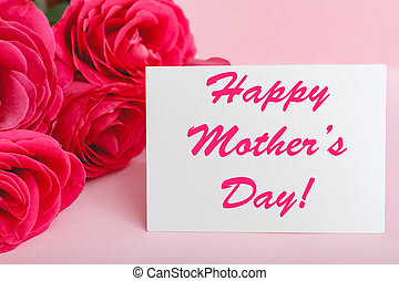 Happy Mothers Day text on gift card in flower bouquet of pink roses on pink background. Greeting card for Mom. Flower delivery, Congratulations card in flowers for women. Greeting card in roses