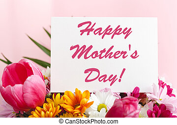 Happy Mothers Day text on gift card in flower bouquet on pink background. Greeting card for Mom. Flower delivery, Congratulations card in flowers for women. Greeting card in pink tulips.