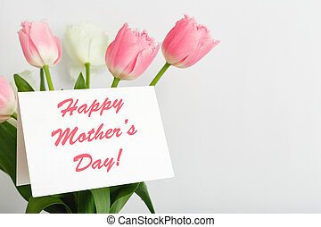 Happy Mothers Day text on gift card in flower bouquet on white background. Greeting card for Mom. Flower delivery, Congratulations card in flowers for women. Greeting card in pink tulips.