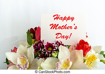 Happy Mothers Day text on gift card in flower bouquet on white background. Greeting card for Mom. Flower delivery, Congratulations card in flowers for women. Greeting card in tulips, orchids bouquet.