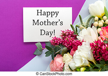 Happy Mothers Day text on gift card with flower bouquet of roses, tulips, eucalyptus on purple background. Greeting card for Mom. Flower delivery, Congratulations Greeting card and flowers for mother.