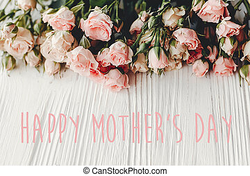 Happy Mother's Day text sign at pink small roses on wooden background, space for text. Tender Flower border, Floral greeting card. Mothers day.