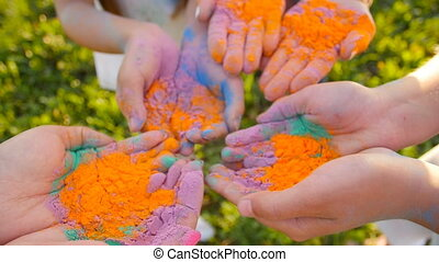 Happy mothers with children having fun with colorful powder...