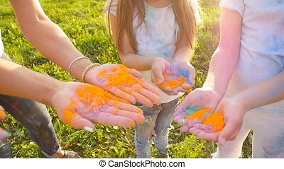 Happy mothers with children having fun with colorful powder at holi festival of colors