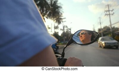 Happy motorcyclist wearing sunglasses drives motorcycle on...