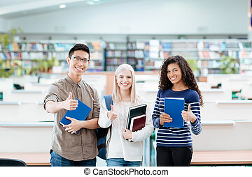 Happy multi etchnic students standing in university library