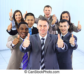 Happy multi-ethnic business team with thumbs up in the ...