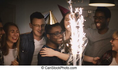Happy multi ethnic friends on a birthday party. Sparkling Bengal firework cake candles. Diverse group celebration.