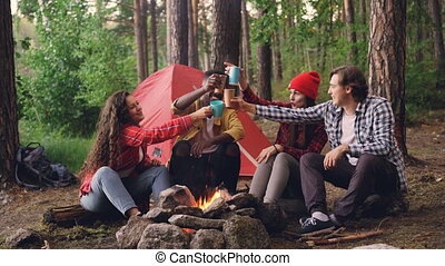 Happy multi-ethnic group of travelers clinking glasses with...