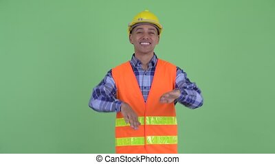 Happy multi ethnic man construction worker dancing
