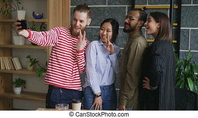 Happy multi-ethnic team taking selfie in modern loft office....