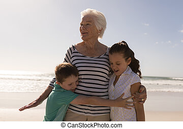 Happy multi-generation family embracing on beach
