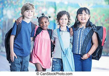 Happy multi race classroom embracing in the schoolyard.