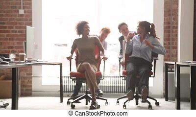 Happy multicultural office workers laughing having fun riding on chairs