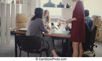 Happy multiethnic business people meeting. Female secretary...