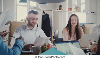 Happy multiethnic business people meeting in office. Female manager gives documents to employees at trendy workplace 4K.