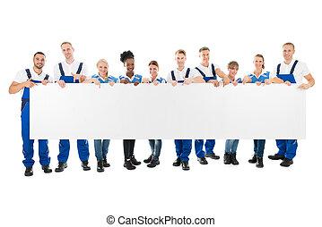 Happy Multiethnic Cleaners Holding Blank Billboard