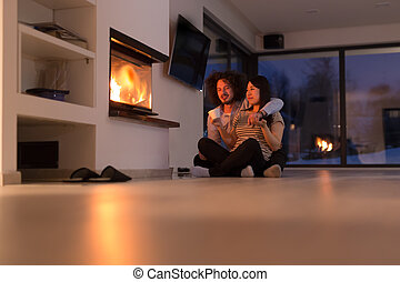 happy multiethnic couple sitting in front of fireplace -...